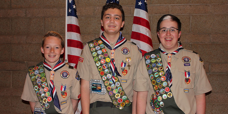 Three young boy scouts pose in front of American flags