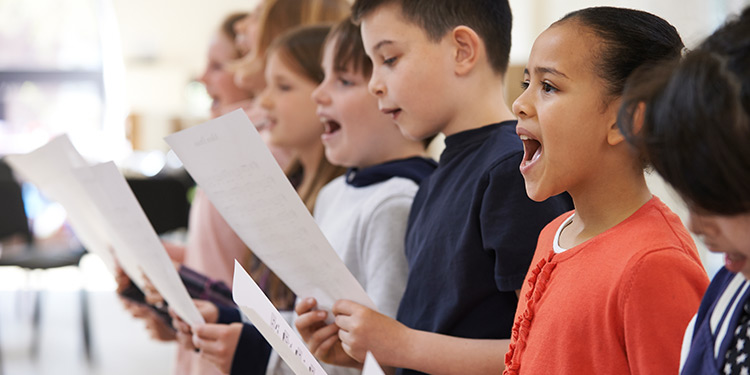 Children holding sheet music and singing