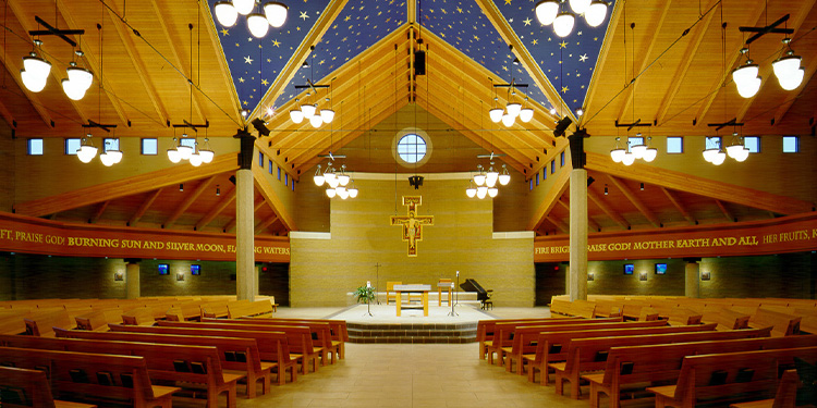Interior of Saint Francis church; view of pews, altar, cross, and starry ceiling