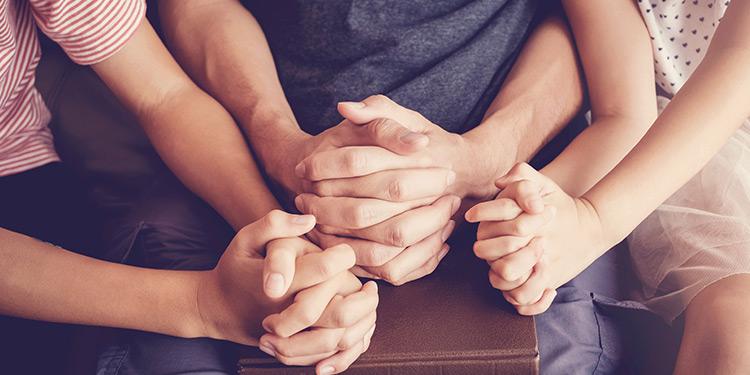 Closeup of family praying together