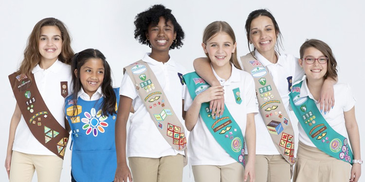 Six girl scouts wearing sashes and badges smile for photo