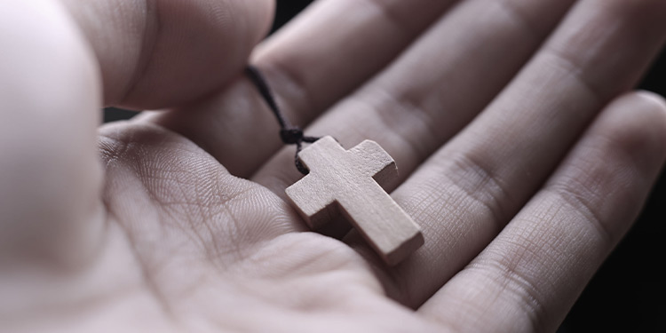 Hand holding a small wooden cross