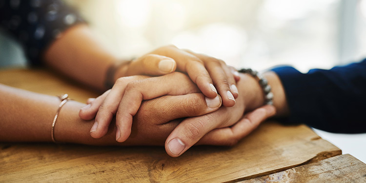 Two people holding hands across a wooden table