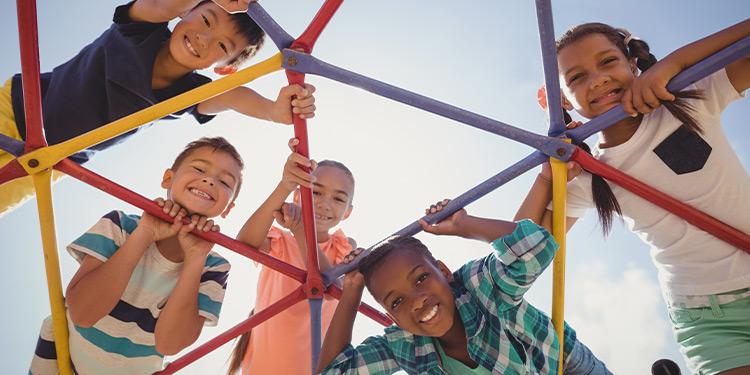 Five children smile and play on a jungle gym