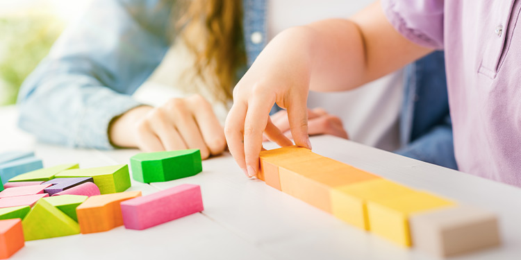 Closeup of child playing with colorful wooden blocks