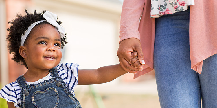 Young toddler girl smiles and holds her mom's hand