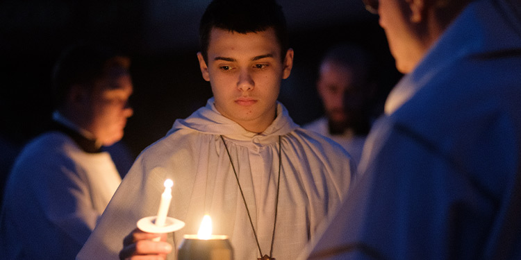 Young man in white robe holds a lit candle