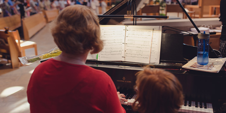 Back view of woman and child sitting at a piano; members attending mass can be seen in the background