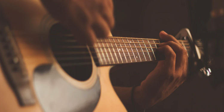 Closeup on hands playing an acoustic guitar