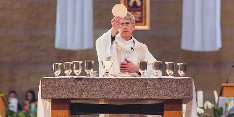 Pastor standing at chalice table holding up a wafer