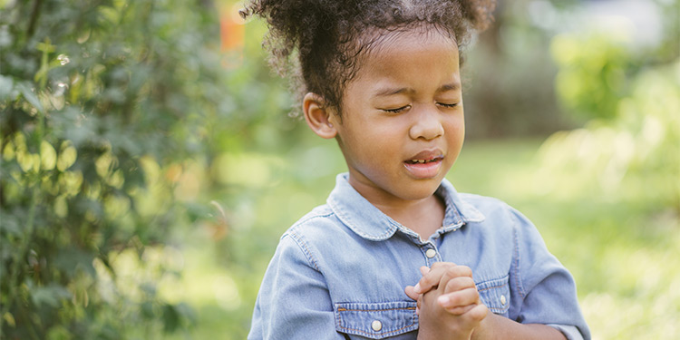 Young girl praying with her eyes closed