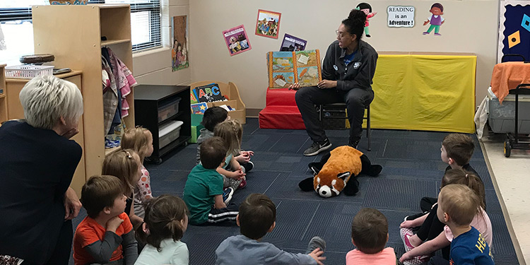 Preschool students sit on floor while teacher reads a story to them