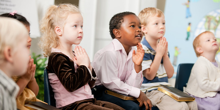 Young students sit and pray