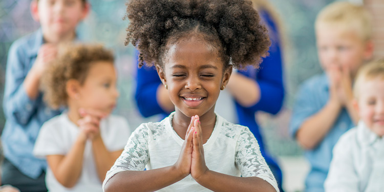 Young girl hold her hands together in prayer and smiles