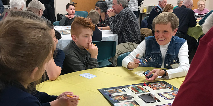 Kids and senior members of Saint Francis play board games together