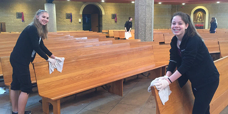 Two female high school students smile and wipe down the pews