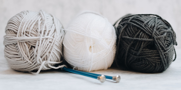 Three balls of yarn with two knitting needles tucked underneath them