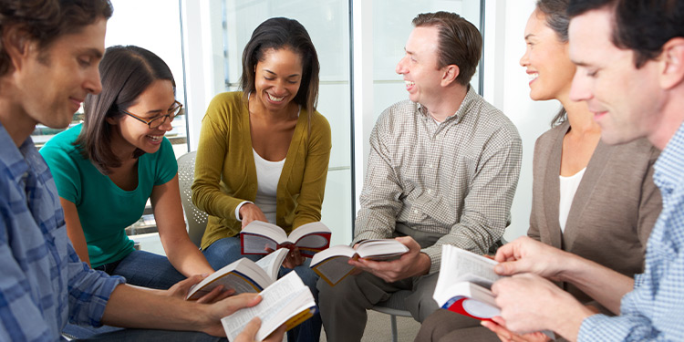 Group of young adults sits in circle and studies bible together